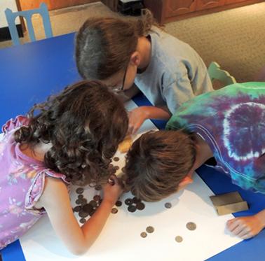 kids examine coins